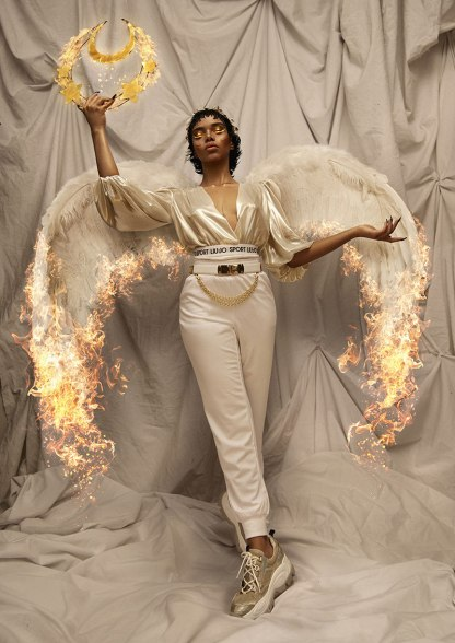 Black woman stands leaning back, balanced on right leg with left leg pointing forwards. She wears white feathery wings with fiery ends, a silky cream top, short white trousers, and sneakers, and carries a glowing wreath in raised right hand.