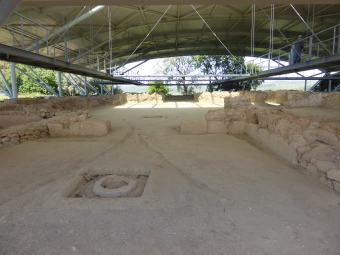 Excavated ruins of porch area, with column base front and centre, low walls, and doorway leading into courtyard. Modern suspended walkway is visible above.