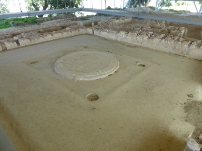 Square room with large circular hearth in the centre, surrounded by four pillar holes. Low walls can be seen around the far side of the room. A small rectangular depression is visible in the middle of the far right wall.