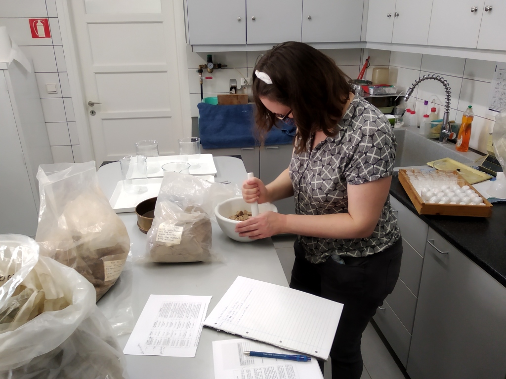 Woman standing at a table in a laboratory with large sacks of dry clay on it, grinding clay with a pestle and mortar