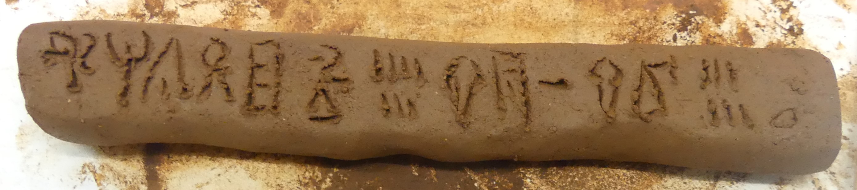 Long, thin clay tablet with large Linear B signs inscribed on its flat top surface