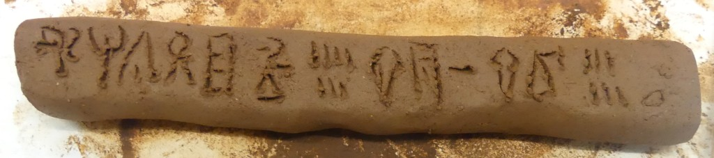 Long thin clay tablet with Linear B signs incised on the flat top surface. Loose clay can be seen around the edges of the strokes which form the signs.