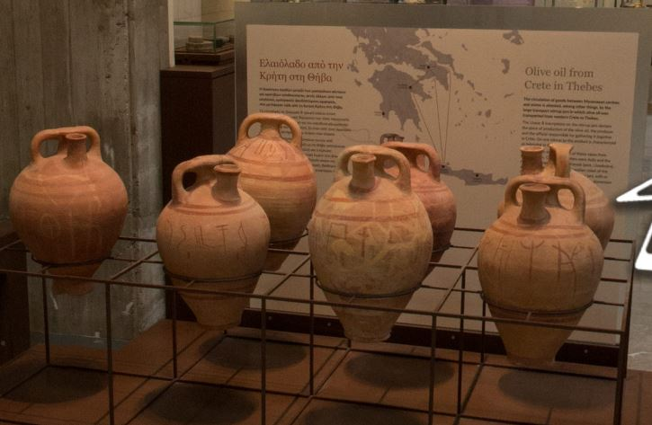 Display of 7 large jars with stirrup-shaped handles and spouts at the top, painted with Linear B inscriptions around the belly, resting off the ground in a frame. Behind is a text panel headed 'Olive oil from Crete in Thebes'