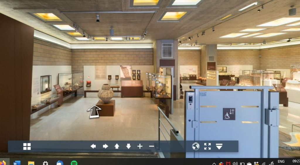 virtual view from entrance to gallery: straight ahead are display cases around walls and a large jar in the centre; to right is wheelchair lift down and further cases beyond it