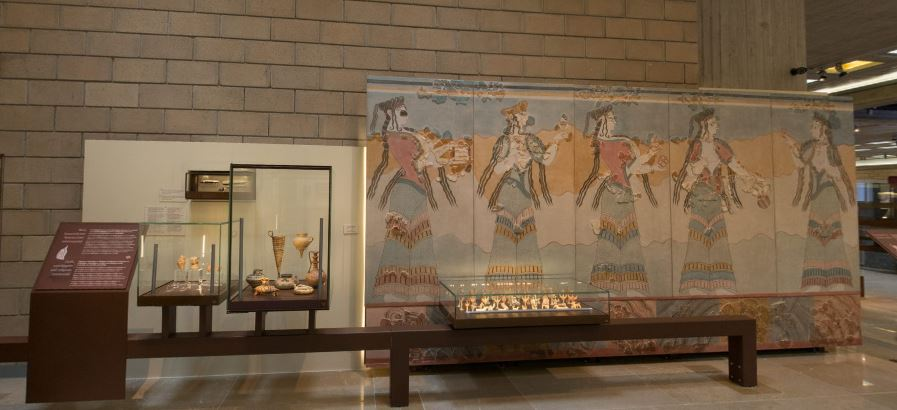 Display with three small cases containing vases and Linear B tablets on left, with display board; to right is a large colourful reconstructed fresco of women carrying various items in a procession, with a low case containing small clay figurines in front