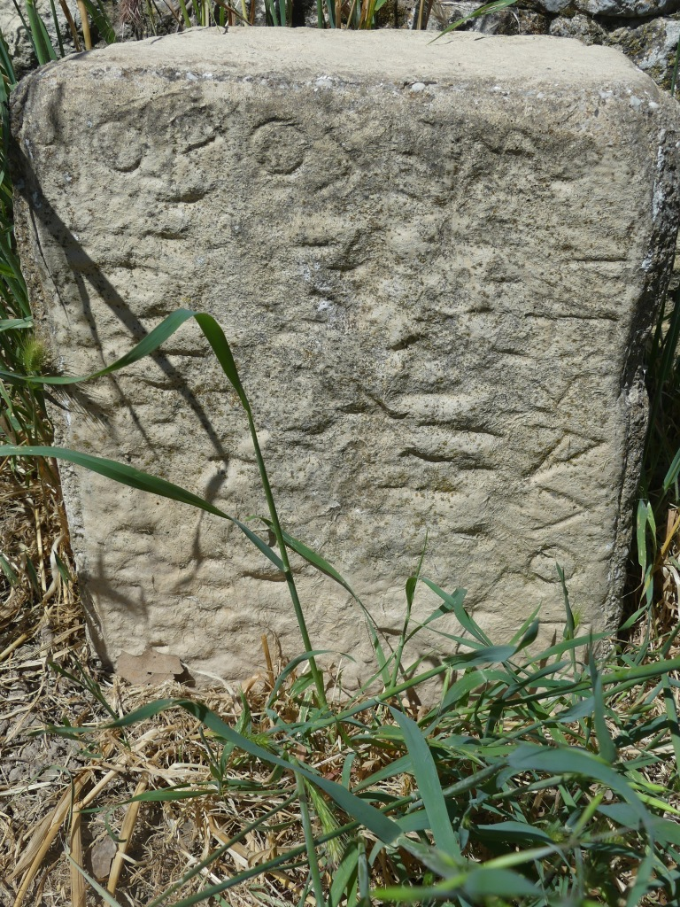 Upright rectangular stone sitting amongst grass, with engraved letters running along top edge and down right-hand edge