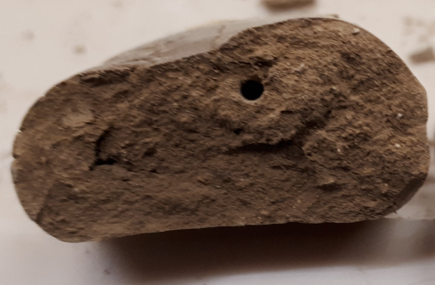 Broken edge of clay tablet, with a round hole in it