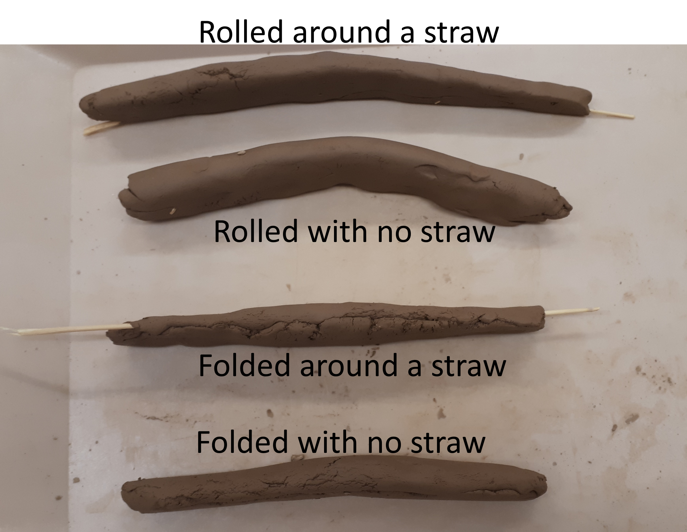 """Four long thin clay tablets positioned upright on their sides. top to bottom: caption """"rolled around a straw"""", tablet slightly bent with straw sticking out both ends. caption """"rolled with no straw"""", very bent tablet. """"folded around a straw"""": almost completely straight tablet with seam visible along uppermost edge, and straw sticking out both ends. """"folded with no straw"""": very slightly bent tablet with seam partly visible on edge"""