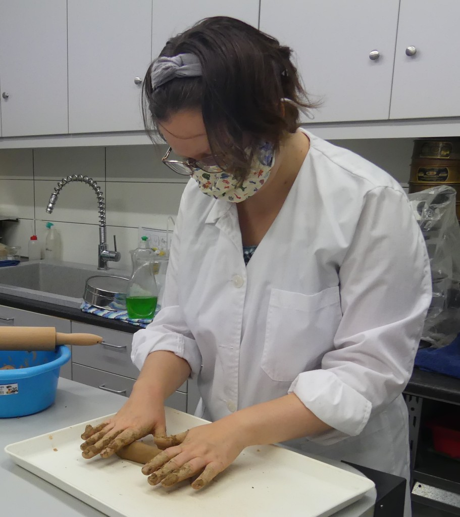 Picture of Anna standing at table in laboratory wearing lab coat. She is using both hands to roll out a cylinder of clay on a plastic tray on the table